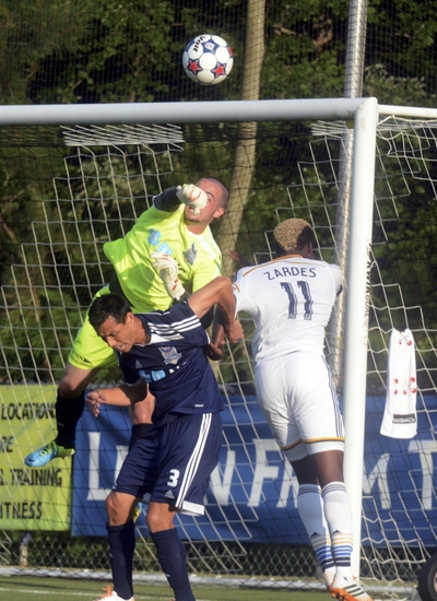 Jun 24, 2014; Cary, NC, USA; Carolina Railhawks goalkeeper Scott Goodwin (12) punches the ball away from Los Angeles Galaxy forward Gyasi Zardes (11) during the US Open Cup fifth round at WakeMed Soccer Park. Mandatory Credit: Rob Kinnan-USA TODAY Sports