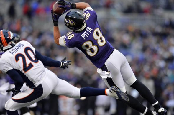 Dec 16 2012; Baltimore, MD, USA; Baltimore Ravens tight end Dennis Pitta (88) brings in a touchdown reception as he is defended by Denver Broncos strong safety Mike Adams (20) at M&T Bank Stadium.  The Broncos defeated the Ravens 34-17. Mandatory Credit: Ron Chenoy-USA TODAY Sports