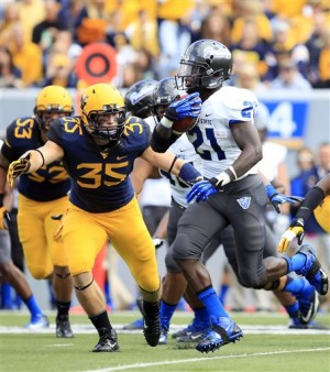 Georgia State running back Travis Evans (21) carries the ball past West Virginia's Nick Kwiatkoski (35) during the first quarter of an NCAA college football game in Morgantown, W.Va., on Saturday, Sept. 14, 2013. West Virginia won 41-7. (AP Photo/Christopher Jackson)