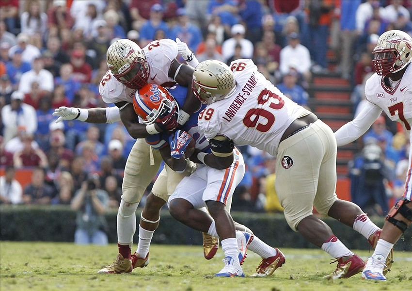 Nov 30, 2013; Gainesville, FL, USA; Florida State Seminoles linebacker Telvin Smith (22) and defensive tackle Nile Lawrence-Stample (99) tackle Florida Gators running back Kelvin Taylor (21) during the second half at Ben Hill Griffin Stadium. Florida State Seminoles defeated the Florida Gators 37-7. Mandatory Credit: Kim Klement-USA TODAY Sports