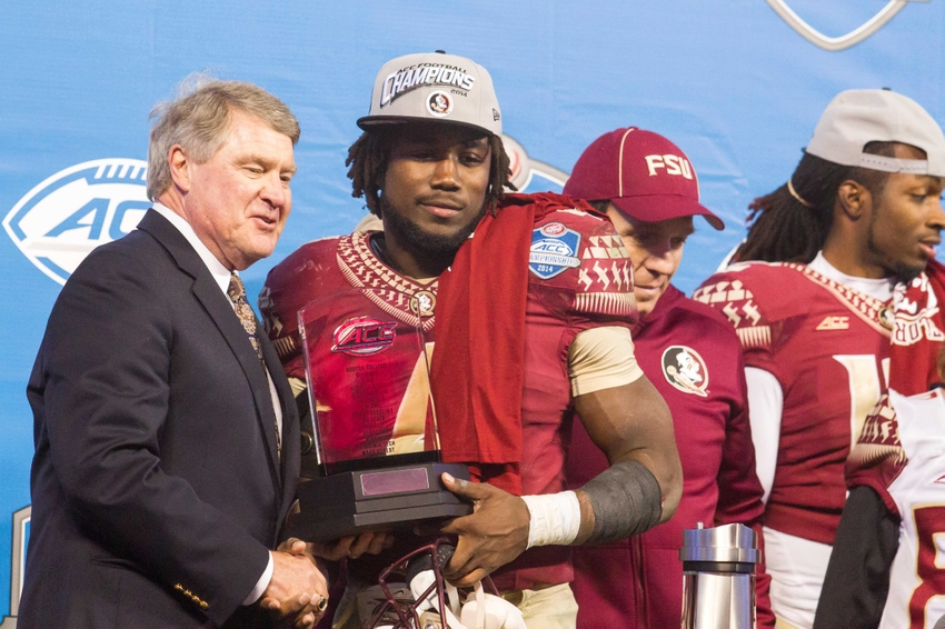 Dec 6, 2014; Charlotte, NC, USA; ACC commissioner John Swofford shakes hands with MVP Florida State Seminoles running back Dalvin Cook (4) after defeating the Georgia Tech Yellow Jackets at Bank of America Stadium. FSU defeated Georgia Tech 37-35. Mandatory Credit: Jeremy Brevard-USA TODAY Sports