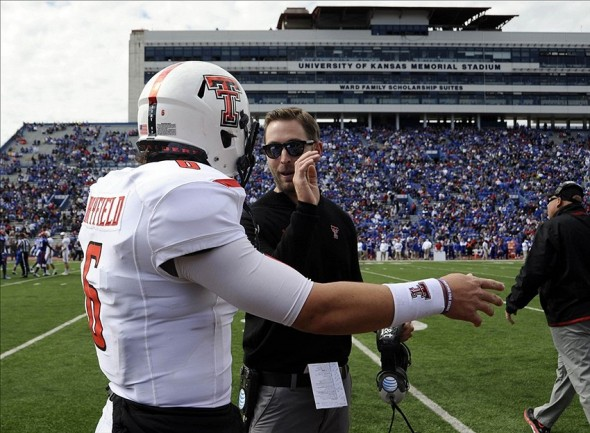 Oct 5, 2013; Lawrence, KS, USA; Texas Tech Red Raiders head coach Kliff Kingsbury (right) talks to quarterback Baker Mayfield (6) after a score against the Kansas Jayhawks in the second half at Memorial Stadium. Texas Tech won the game 54-16. Mandatory Credit: John Rieger-USA TODAY Sports