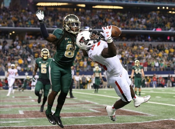 Nov 16, 2013; Arlington, TX, USA; Texas Tech Red Raiders receiver Eric Ward (18) catches a touchdown pass in the first quarter against Baylor Bears cornerback K.J. Morton (8) at AT