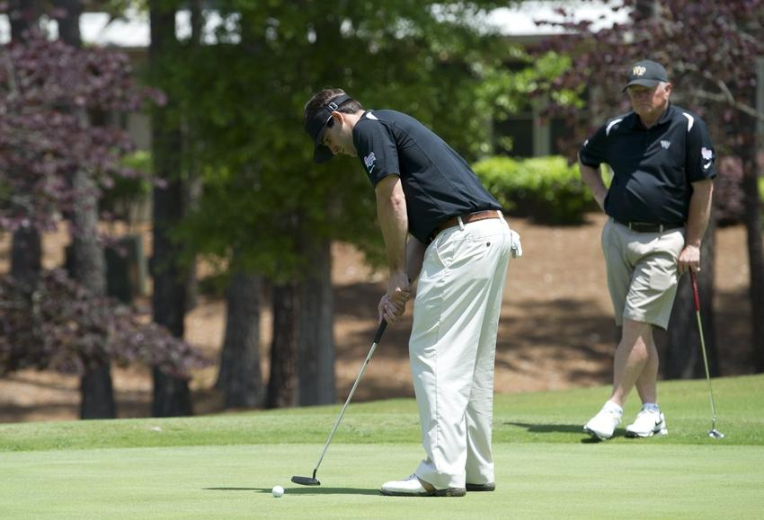 Apr 30, 2013; Greensboro, GA, USA; Wake Forest Demon Deacons former quarterback Riley Skinner putts as Wake Forest Demon Deacons head football coach Jim Grobe watches (right) during the Chick-fil-A Challenge at the Reynolds Plantation Resort. Mandatory Credit: Paul Abell/CFA-pr via USA TODAY Sports **HAND OUT PHOTO **