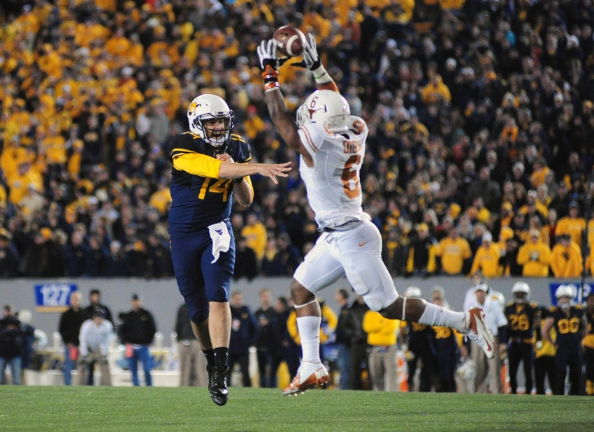 Nov 9, 2013; Morgantown, WV, USA; West Virginia Mountaineers quarterback Paul Millard (14) has his pass deflected by Texas Longhorns cornerback Quandre Diggs (6) in overtime at Milan Puskar Stadium. Mandatory Credit: Evan Habeeb-USA TODAY Sports