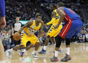 Mar 19, 2014; Denver, CO, USA; Detroit Pistons power forward Greg Monroe (10) guards Denver Nuggets point guard Aaron Brooks (0) in the third quarter at the Pepsi Center. The Nuggets won 118-109. Mandatory Credit: Isaiah J. Downing-USA TODAY Sports