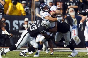 Nov 6, 2011; Oakland, CA, USA; Denver Broncos quarterback Tim Tebow (15) is tackled by Oakland Raiders defensive end Lamarr Houston (99) during the second quarter at O.co Coliseum. Mandatory Credit: Jason O. Watson-USA TODAY Sports