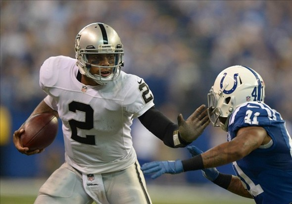 Sep 8, 2013; Indianapolis, IN, USA; Oakland Raiders quarterback Terrelle Pryor (2) tries to elude Indianapolis Colts safety Antoine Bethea (41) at Lucas Oil Stadium. Mandatory Credit: Kirby Lee-USA TODAY Sports