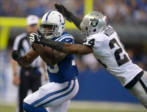 Sep 8, 2013; Indianapolis, IN, USA; Oakland Raiders cornerback Charles Woodson (24) tackles Indianapolis Colts running back Vick Ballard (33) at Lucas Oil Stadium. Mandatory Credit: Kirby Lee-USA TODAY Sports