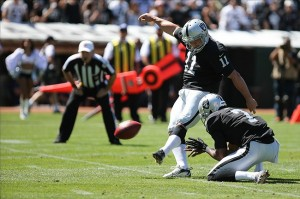 Sep 15, 2013; Oakland, CA, USA; Oakland Raiders kicker Sebastian Janikowski (11) kicks the extra point with a hold by punter Marquette King (7) against the Jacksonville Jaguars during the first quarter at O.co Coliseum. Mandatory Credit: Kelley L Cox-USA TODAY Sports