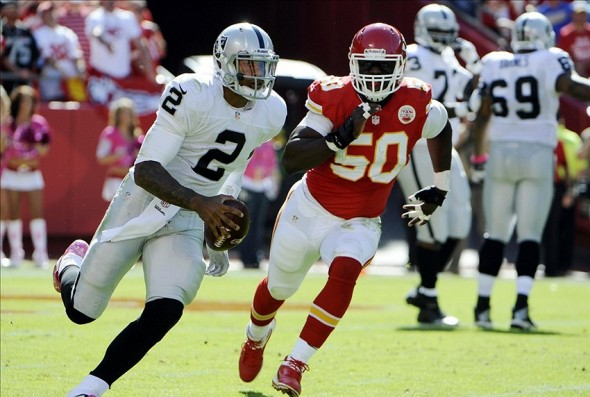 Oct 13, 2013; Kansas City, MO, USA; Oakland Raiders quarterback Terrelle Pryor (2) is chased by Kansas City Chiefs outside linebacker Justin Houston (50) in the second half at Arrowhead Stadium. Kansas City won the game 24-7. Mandatory Credit: John Rieger-USA TODAY Sports