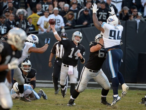 Nov 24, 2013; Oakland, CA, USA; Oakland Raiders quarterback Matt McGloin (14) throws a pass against the Tennessee Titans at O.co Coliseum. The Titans defeated the Raiders 23-19. Mandatory Credit: Kirby Lee-USA TODAY Sports