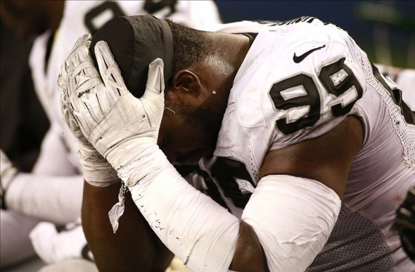 Nov 28, 2013; Arlington, TX, USA; Oakland Raiders defensive end Lamarr Houston (99) reacts after the game against the Dallas Cowboys on Thanksgiving at AT