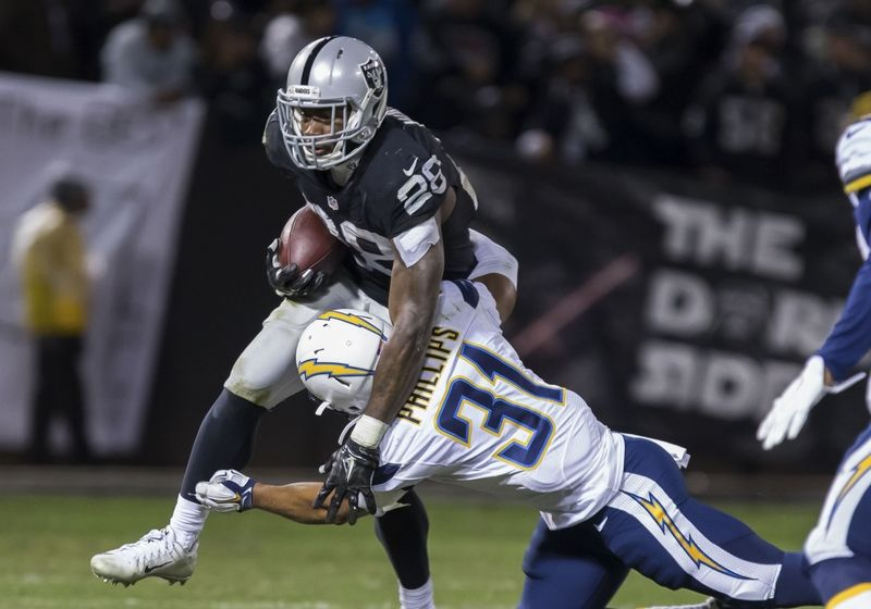 Dec 24, 2015; Oakland, CA, USA; Oakland Raiders running back Latavius Murray (28) carries the ball against San Diego Chargers cornerback Adrian Phillips (31) during the third quarter at O.co Coliseum. The Oakland Raiders defeated the San Diego Chargers 23-20. Mandatory Credit: Kelley L Cox-USA TODAY Sports
