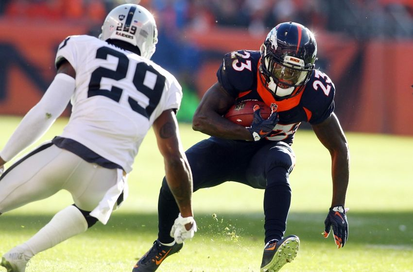 Dec 13, 2015; Denver, CO, USA; Denver Broncos running back Ronnie Hillman (23) runs the ball against Oakland Raiders cornerback David Amerson (29) during the first half at Sports Authority Field at Mile High. Mandatory Credit: Chris Humphreys-USA TODAY Sports