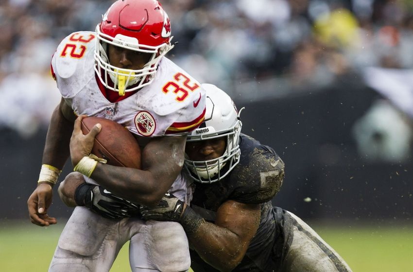 Oct 16, 2016; Oakland, CA, USA; Kansas City Chiefs running back Spencer Ware (32) is brought down by Oakland Raiders middle linebacker Cory James (57) during the third quarter at Oakland Coliseum. The Kansas City Chiefs defeated the Oakland Raiders 26-10. Mandatory Credit: Kelley L Cox-USA TODAY Sports