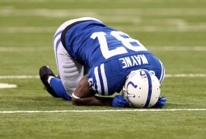 Oct 20, 2013; Indianapolis, IN, USA; Indianapolis Colts wide receiver Reggie Wayne (87) reacts after sustaining an injury against the Denver Broncos in the 2nd half during the game at Lucas Oil Stadium. Mandatory Credit: Brian Spurlock-USA TODAY Sports