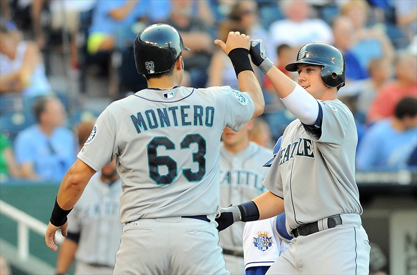 July 16, 2012; Kansas City, MO, USA; Seattle Mariners first baseman Justin Smoak (17) is congratulated by designated hitter Jesus Montero (63) after Smoak hit a home run in the first inning of the game against the Kansas City Royals at Kauffman Stadium. Mandatory Credit: Denny Medley-USA TODAY Sports