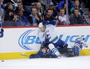 Mar 27, 2014; Denver, CO, USA; Vancouver Canucks left wing David Booth (7) falls on Colorado Avalanche center Matt Duchene (9) as they battle for the puck during the second period at Pepsi Center. Mandatory Credit: Chris Humphreys-USA TODAY Sports