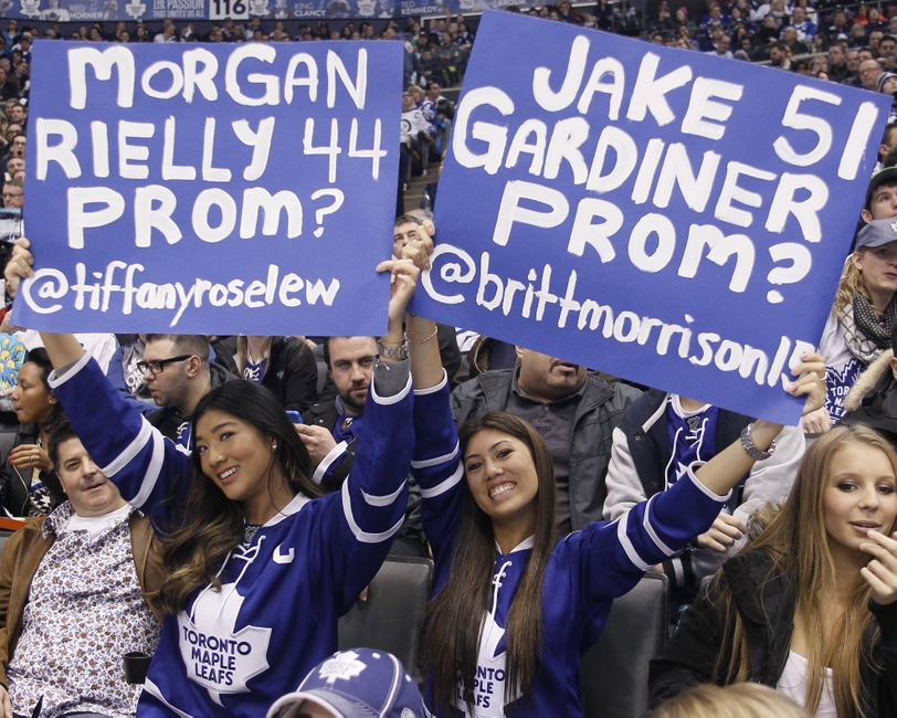 Apr 5, 2014; Toronto, Ontario, CAN; Toronto Maple Leafs fans Tiffany Lew (left) and Brittany Morrison (right) hold up signs for their favourite Leaf players during a game against the Winnipeg Jets at the Air Canada Centre. Winnipeg defeated Toronto 4-2. Mandatory Credit: John E. Sokolowski-USA TODAY Sports