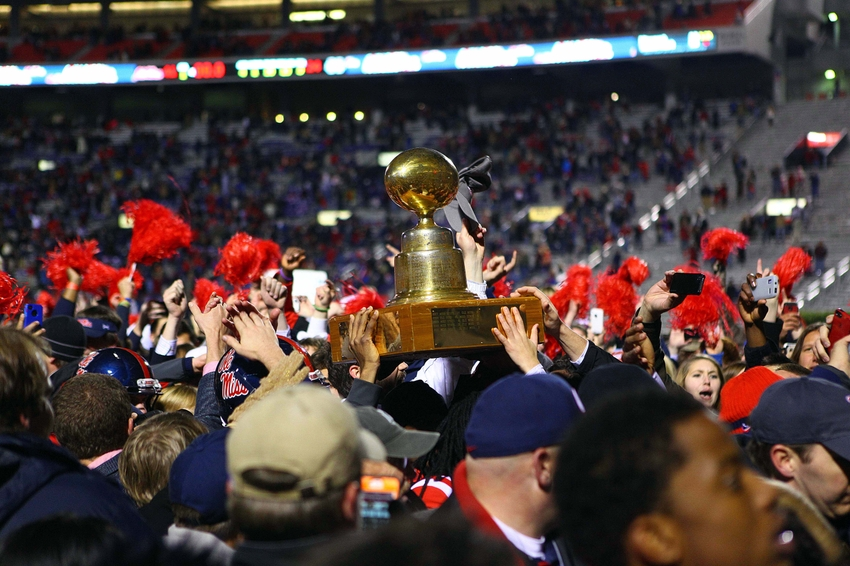 Nov 24, 2012; Oxford, MS, USA;  Mississippi Rebels fans celebrate by holding up the Egg Bowl trophy after their victory against the Mississippi State Bulldogs at Vaught-Hemingway Stadium.   Mississippi Rebels defeated the Mississippi State Bulldogs 41-24.  Mandatory Credit: Spruce Derden-USA TODAY Sports