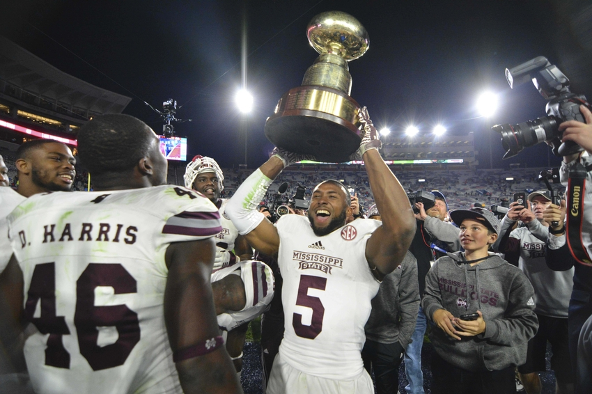 Nov 26, 2016; Oxford, MS, USA;  Mississippi State Bulldogs players celebrate with the Egg Bowl trophy after the game against the Mississippi Rebels at Vaught-Hemingway Stadium. Mississippi State won 55-20 Mandatory Credit: Matt Bush-USA TODAY Sports