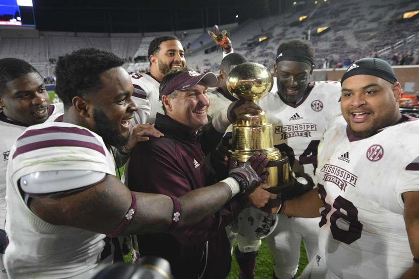 Nov 26, 2016; Oxford, MS, USA; Mississippi State Bulldogs head coach Dan Mullen and players celebrate with the Egg Bowl trophy after the game against the Mississippi Rebels at Vaught-Hemingway Stadium. Mississippi State won 55-20 Mandatory Credit: Matt Bush-USA TODAY Sports