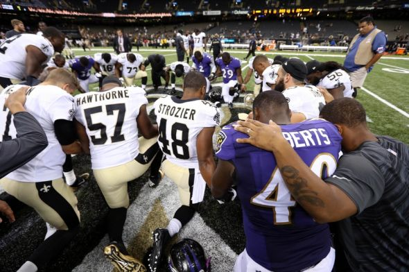 Aug 28, 2014; New Orleans, LA, USA; New Orleans Saints and Baltimore Ravens players kneel in prayer at the conclusion of their game at the Mercedes-Benz Superdome. The Ravens won, 22-13. Mandatory Credit: Chuck Cook-USA TODAY Sports