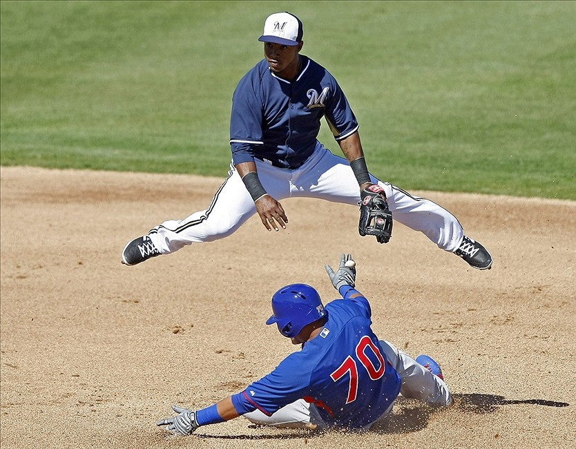 Mar 3, 2014; Phoenix, AZ, USA; Milwaukee Brewers shortstop Jean Segura (9) turns the double play while avoiding Chicago Cubs shortstop Javier Baez (70) during the fourth inning at Maryvale Baseball Park. Mandatory Credit: Rick Scuteri-USA TODAY Sports