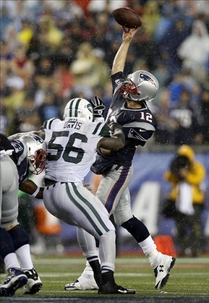 Sep 12, 2013; Foxborough, MA, USA; New England Patriots quarterback Tom Brady (12) makes a pass under pressure by New York Jets inside linebacker DeMario Davis (56) during the fourth quarter at Gillette Stadium. The New England Patriots won 13-10. Mandatory Credit: Greg M. Cooper-USA TODAY Sports