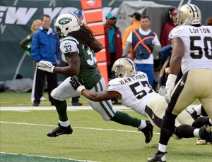 Nov 3, 2013; East Rutherford, NJ, USA; New York Jets running back Chris Ivory (33) scores a touchdown past New Orleans Saints outside linebacker David Hawthorne (57) in the first half during the game at MetLife Stadium. Mandatory Credit: Robert Deutsch-USA TODAY Sports