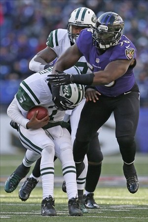 Nov 24, 2013; Baltimore, MD, USA; Baltimore Ravens linebacker Elvis Dumervil (58) tackles New York Jets quarterback Geno Smith (7) in the first half at M