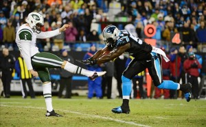 Dec 15, 2013; Charlotte, NC, USA; New York Jets punter Ryan Quigley (1) has his punt blocked by Carolina Panthers linebacker Jason Williams (54) in the fourth quarter at Bank of America Stadium. Mandatory Credit: Bob Donnan-USA TODAY Sports