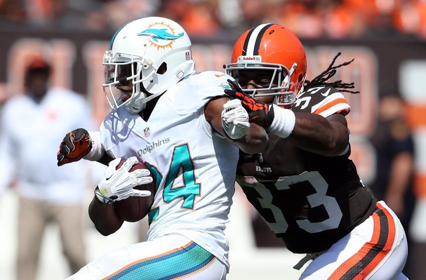 Sep 8, 2013; Cleveland, OH, USA; Miami Dolphins cornerback Dimitri Patterson (24) returns an interception as he his hit by Cleveland Browns running back Trent Richardson (33) during the second quarter at FirstEnergy Field. Mandatory Credit: Ron Schwane-USA TODAY Sports