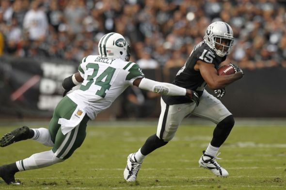 Nov 1, 2015; Oakland, CA, USA; Oakland Raiders wide receiver Michael Crabtree (15) tries to elude New York Jets strong safety Dion Bailey (34) after making a catch in the fourth quarter at O.co Coliseum. The Raiders defeated the Jets 34-20. Mandatory Credit: Cary Edmondson-USA TODAY Sports