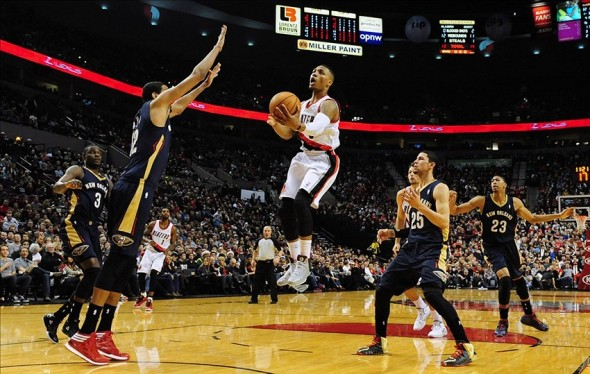 Dec 21, 2013; Portland, OR, USA; Portland Trail Blazers point guard Damian Lillard (0) drives to the basket on New Orleans Pelicans forward Alexis Ajinca (12) and shooting guard Austin Rivers (25) during the first quarter of the game at the Moda Center. Mandatory Credit: Steve Dykes-USA TODAY Sports