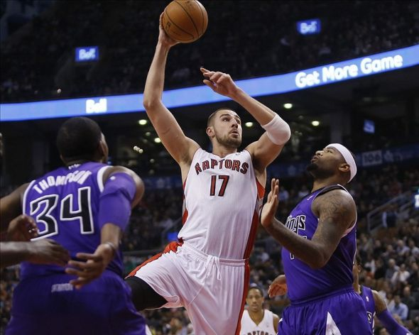 Mar 7, 2014; Toronto, Ontario, CAN; Toronto Raptors center Jonas Valanciunas (17) goes up to make a basket against Sacramento Kings forward-center Jason Thompson (34) and center DeMarcus Cousins (15) during the first half at Air Canada Centre. Mandatory Credit: John E. Sokolowski-USA TODAY Sports