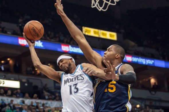 Apr 16, 2014; Minneapolis, MN, USA; Utah Jazz center Derrick Favors (15) fouls Minnesota Timberwolves forward Corey Brewer (13) in the first quarter at Target Center. Mandatory Credit: Brad Rempel-USA TODAY Sports