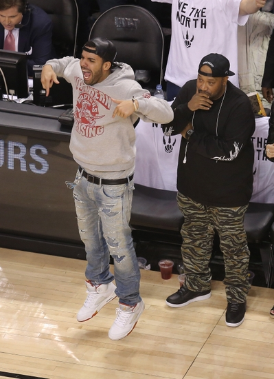 May 4, 2014; Toronto, Ontario, CAN; Toronto Raptors ambassador and rap artist Drake celebrates a basket against the Brooklyn Nets in game seven of the first round of the 2014 NBA Playoffs at Air Canada Centre. The Nets beat the Raptors 104-103. Mandatory Credit: Tom Szczerbowski-USA TODAY Sports
