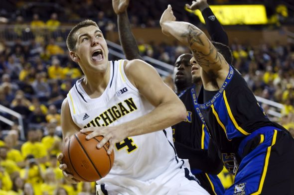 Nov 29, 2013; Ann Arbor, MI, USA; Michigan Wolverines forward Mitch McGary (4) is defended by Coppin State Eagles forward Zach Burnham in the second half at Crisler Arena. Michigan won 87-45. Mandatory Credit: Rick Osentoski-USA TODAY Sports