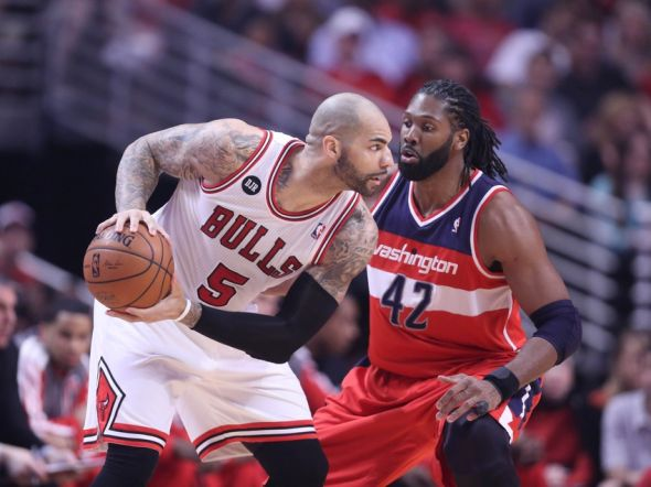 Apr 20, 2014; Chicago, IL, USA; Chicago Bulls forward Carlos Boozer (5) is defended by Washington Wizards forward Nene Hilario (42) during the first quarter of game one of the first round of the 2014 NBA Playoffs at the United Center. Mandatory Credit: Dennis Wierzbicki-USA TODAY Sports