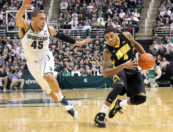 Mar 6, 2014; East Lansing, MI, USA; Iowa Hawkeyes guard Roy Devyn Marble (4) drives to the basket against Michigan State Spartans guard Denzel Valentine (45) during the 1st half of a game at Jack Breslin Student Events Center. Mandatory Credit: Mike Carter-USA TODAY Sports
