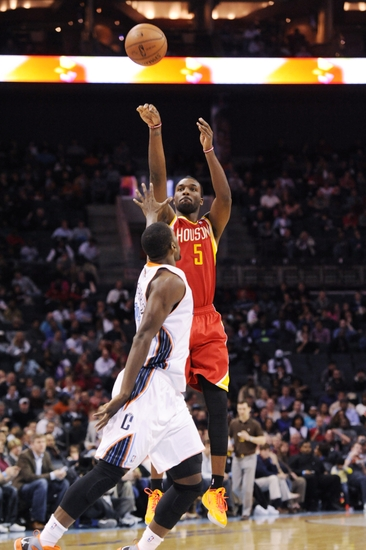 Mar 24, 2014; Charlotte, NC, USA; Houston Rockets forward guard Jordan Hamilton (5) takes a jump shot as he is defended by Charlotte Bobcats forward Michael Kidd-Gilchrist (14) during the first half of the game at Time Warner Cable Arena. Mandatory Credit: Sam Sharpe-USA TODAY Sports