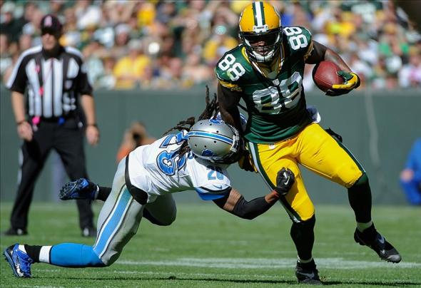 Oct 6, 2013; Green Bay, WI, USA; Green Bay Packers tight end Jermichael Finley (88) is tackled by Detroit Lions safety Louis Delmas (26) in the first quarter at Lambeau Field. Mandatory Credit: Benny Sieu-USA TODAY Sports