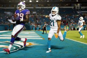 Sep 27, 2015; Miami Gardens, FL, USA; Buffalo Bills running back Karlos Williams scores in the second half as Miami Dolphins corner back Brent Grimes (21) chases in the second half at Sun Life Stadium where Buffalo defeated the Dolphins 41-14. Mandatory Credit: Andrew Innerarity-USA TODAY Sports