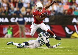 Oct 17, 2013; Phoenix, AZ, USA; Arizona Cardinals wide receiver Andre Roberts (12) leaps over Seattle Seahawks cornerback Jeremy Lane (20) in the first quarter at University of Phoenix Stadium. Mandatory Credit: Mark J. Rebilas-USA TODAY Sports