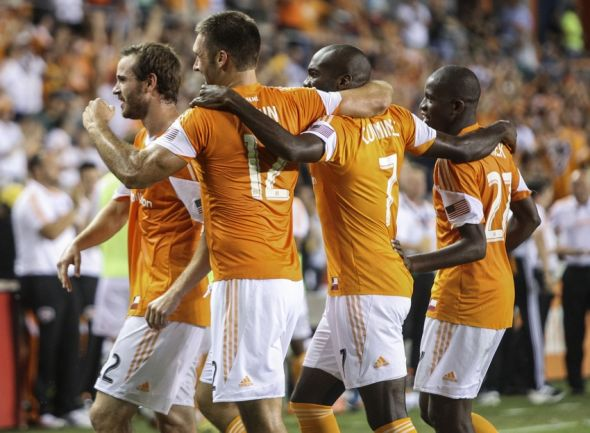 Aug 3, 2014; Houston, TX, USA; Houston Dynamo forward Will Bruin (12) is congratulated by teammates after scoring a goal during the second half against D.C. United at BBVA Compass Stadium. The Dynamo defeated D.C. United 1-0. Mandatory Credit: Troy Taormina-USA TODAY Sports
