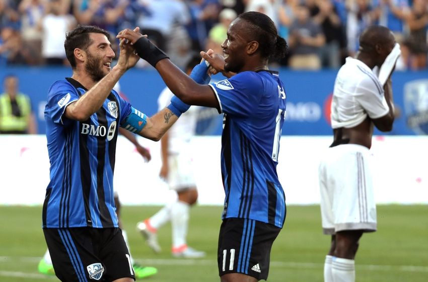Jun 25, 2016; Montreal, Quebec, CAN; Montreal Impact midfielder Ignacio Piatti (10) celebrates with teammate forward Didier Drogba (11) after scoring a goal against Sporting Kansas City during the first half at Stade Saputo. Mandatory Credit: Jean-Yves Ahern-USA TODAY Sports