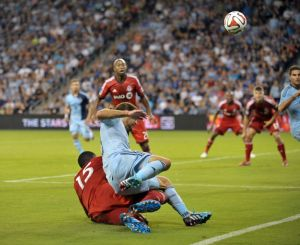 Sporting KC's Graham Zusi is taken down by a TFC defender