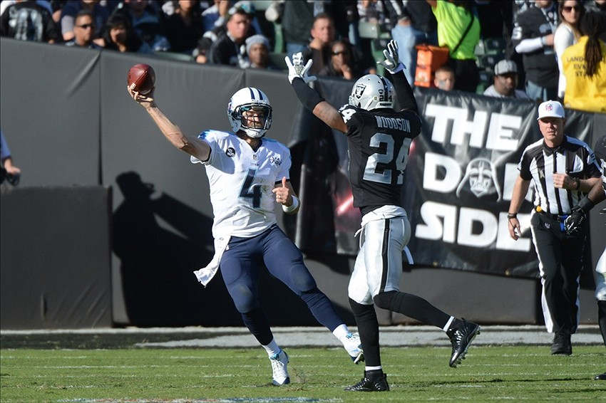 November 24, 2013; Oakland, CA, USA; Tennessee Titans quarterback Ryan Fitzpatrick (4) passes the ball against Oakland Raiders free safety Charles Woodson (24) during the second quarter at O.co Coliseum. Mandatory Credit: Kyle Terada-USA TODAY Sports